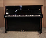 Piano for sale.  Yamaha LX-113 upright piano for sale with a black case and walnut detail. Piano has an eighty-eight note keyboard and three pedals.