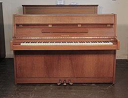 A 1980, Yamaha M5J upright piano with a satin, walnut case