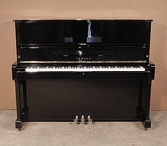 A 1975, Yamaha U1 upright piano with a black case and polyester finish. Piano has an eighty-eight note keyboard and three pedals.