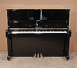 Piano for sale. A 1975, Yamaha U1 upright piano with a black case and polyester finish. Piano has an eighty-eight note keyboard and three pedals.