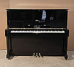 Piano for sale. A 1978, Yamaha U1 upright piano with a black case and polyester finish. Piano has an eighty-eight note keyboard and three pedals.