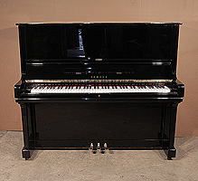 A 1976, Yamaha U3 upright piano with a black case and brass fittings