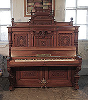 Neoclassical style, Julius Deesz upright piano for sale with an ornately carved, mahogany case. Cabinet features panels carved with scrolling foliage and heraldic crests in high relief, carved corinthian pilasters and a central cherubs head.