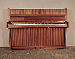 Alexander Herrmann upright piano with a satin, mahogany case. Piano has an eighty-five note keyboard and and two pedals