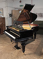 A restored, Bechstein Model A grand piano with a black case and turned legs