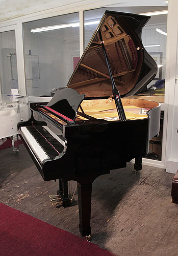 A Besbrode Model 166 grand piano with a black case and spade legs. Piano has a three-pedal lyre and an eighty-eight note keyboard.