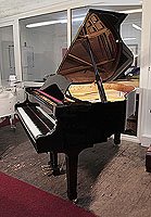 Besbrode Model 166 grand piano with a black case and spade legs. Piano has a three-pedal lyre and an eighty-eight note keyboard.