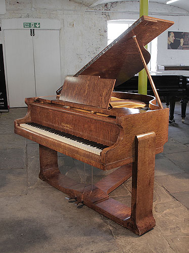 Piano for sale. A 1936, Art Deco style, Chappell baby grand piano for sale with a quilted maple case. Cabinet features sculptural piano legs attached to a cross stretcher.