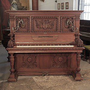 Antique, Georg Fortner upright piano for sale with an ornately carved, mahogany case and ornate candlesticks. Cabinet features carved flowers, foliage, musical instruments and grotesque heads on each piano cheek.
