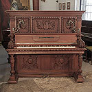 Piano for sale. Antique, Georg Fortner upright piano for sale with an ornately carved, mahogany case and ornate candlesticks. Cabinet features carved flowers, foliage, musical instruments and grotesque heads on each piano cheek