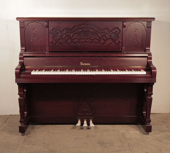 Harmony upright piano for sale with a polished, mahogany case. Cabinet features a carved, arabesque music desk and stylised carvings