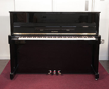 A 2000, Kawai CX-5H upright piano with a black case and polyester finish. Piano has an eighty-eight note keyboard and three pedals.
