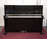 Piano for sale. A 2000, Kawai CX-5H upright piano with a black case and brass fittings
