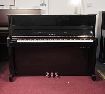 A 2000, Kawai CX-5H upright piano with a black case and fitted Kawai silent system. Piano has an eighty-eight note keyboard and three pedals.