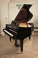 A 2018, Kawai GL-10 baby grand piano for sale with a black case and square, tapered legs. Piano has an eighty-eight note keyboard and a three-pedal lyre.