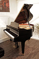 A 2003, Kawai GM-10 baby grand piano for sale with a black case and square, tapered legs. Piano has an eighty-eight note keyboard and a three-pedal lyre.
