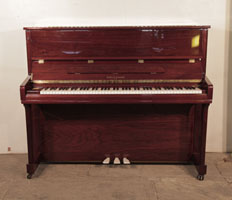 A  Kohler & Campbell upright piano with a walnut case and polyester finish