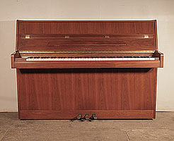 Ottostein CS-108 upright piano with a crown cut, satin, walnut case. Piano has an eighty-eight note keyboard and and three pedals