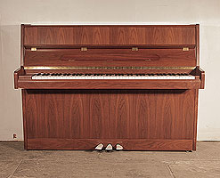Ottostein SU-108P upright piano with a crown cut, satin, walnut case. Piano has an eighty-eight note keyboard and and three pedals