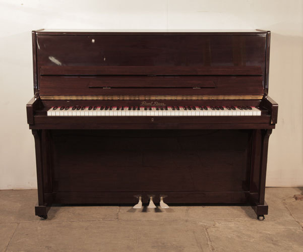 A Pearl River upright piano with a mahogany case .