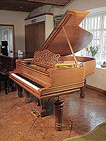 A 1900 Steinway Model A grand piano with a walnut case, filigree music desk and fluted, barrel legs with gadrooning detail.