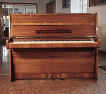 A 1966, Steinway Model Z upright piano with a polished, mahogany case. Piano has an eighty-eight note keyboard and two pedals.