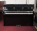 Piano for sale.  Yamaha C110A upright piano with a black case and brass fittings. Piano has an eighty-eight note keyboard and three pedals.