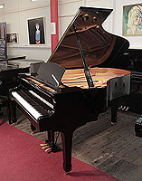 A 2002, Yamaha C3 grand piano for sale with a black case and spade legs. Piano has an eighty-eight note keyboard and a three-pedal lyre.