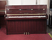 Piano for sale. A 1992, Yamaha M108 upright piano with a mahogany case and polyester finish. Piano has an eighty-eight note keyboard and three pedals.