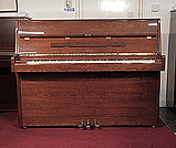 Piano for sale. A 1980, Yamaha P2 upright piano with a walnut case and polyester finish. Piano has an eighty-eight note keyboard and three pedals.