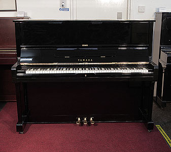 A 1977, Yamaha U1 upright piano with a black case and polyester finish. Piano has an eighty-eight note keyboard and three pedals.