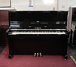 Piano for sale. A 1977, Yamaha U1 upright piano with a black case and polyester finish. Piano has an eighty-eight note keyboard and three pedals.