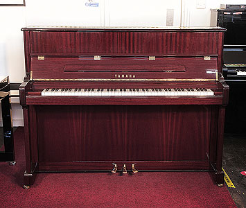 A 2006, Yamaha V118 upright piano with a mahogany case and polyester finish. Piano has an eighty-eight note keyboard and three pedals.