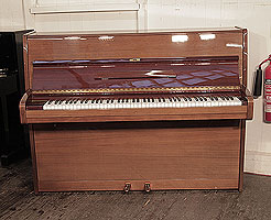 A 1976, Bechstein upright piano with a polished, mahogany case.