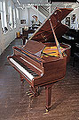 Piano for sale. A Bentley baby grand piano for sale with a walnut case and spade legs. Piano has an eighty-eight note keyboard and a three-pedal lyre.