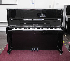 A brand new, Feurich Model 122 upright piano with a black case and chrome fittings