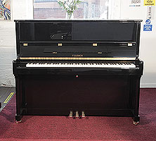 A brand new, Feurich Model 122 upright piano with a black case and brass fittings