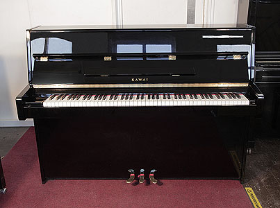 A 2006, Kawai K-15E upright piano with a black case and polyester finish. Piano has an eighty-eight note keyboard and three pedals.