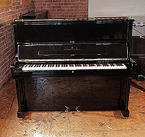 A 1986, Steinway Model V upright piano with a black case and brass fittings