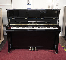 A brand new, Wilh. Steinberg Model AT-K23 upright piano with a black case and brass fittings.
