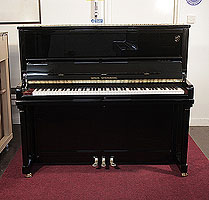 A brand new, Wilh. Steinberg Model AT-K30 upright piano with a black case and brass fittings