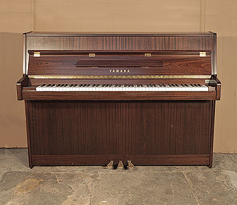 A 1995, Yamaha C108N upright piano with a mahogany case and brass fittings. Piano has an eighty-eight note keyboard and three pedals.