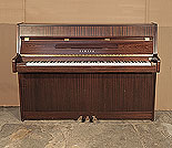 Piano for sale.  A 1995, Yamaha C108N upright piano with a mahogany case and brass fittings. Piano has an eighty-eight note keyboard and three pedals.