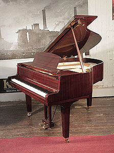 A 1974, Yamaha baby grand piano with a mahogany case and square, tapered legs. Piano has an eighty-eight note keyboard and a two-pedal lyre..