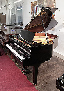 A 1990, Yamaha G1 baby grand piano for sale with a black case and spade legs. Piano has an eighty-eight note keyboard and a three-pedal lyre.
