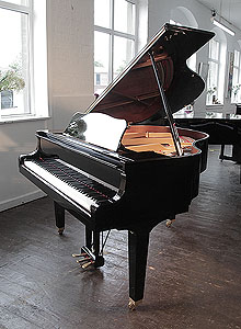 A 2009, Yamaha GB1 baby grand piano for sale with a black case and square, tapered legs.  Piano has an eighty-eight note keyboard and a three-pedal lyre.