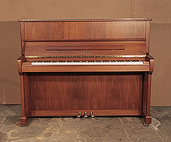 A 2005, Yamaha P121N upright piano with a walnut case and brass fittings