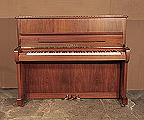 Piano for sale. A 2005, Yamaha P121N upright piano with a walnut case and brass fittings. Piano has an eighty-eight note keyboard and three pedals.