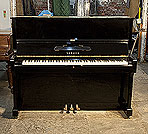 Piano for sale. A 1974, Yamaha U1 upright piano with a black case and polyester finish. Piano has an eighty-eight note keyboard and three pedals.