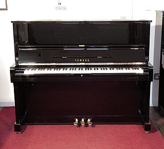 A 1976, Yamaha U1 upright piano with a black case and polyester finish. Piano has an eighty-eight note keyboard and three pedals.